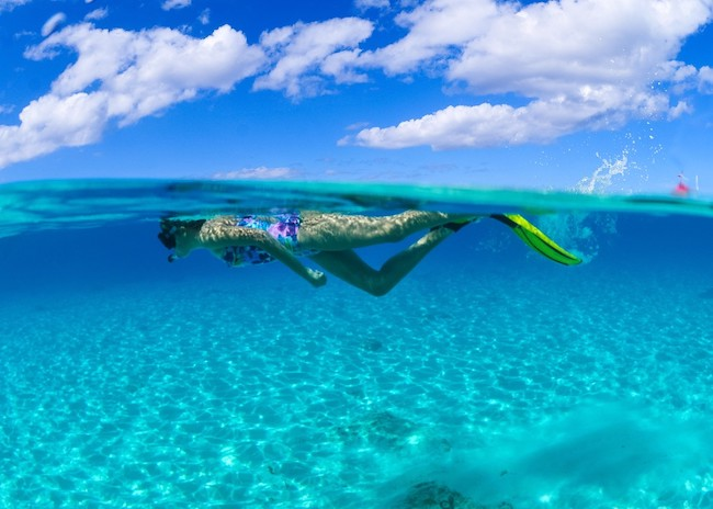 A young girl snorkeling on a reef in the Riviera Maya.