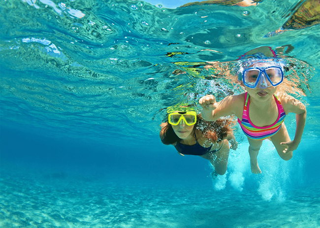 Retha and her kid happily snorkeling during their snorkel trip in Cozumel.