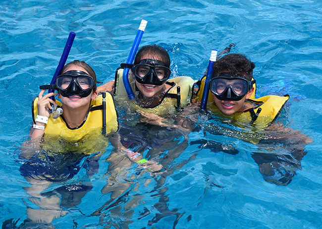 Ricky and his sisters having a fun day during a snorkeling trip with their family.