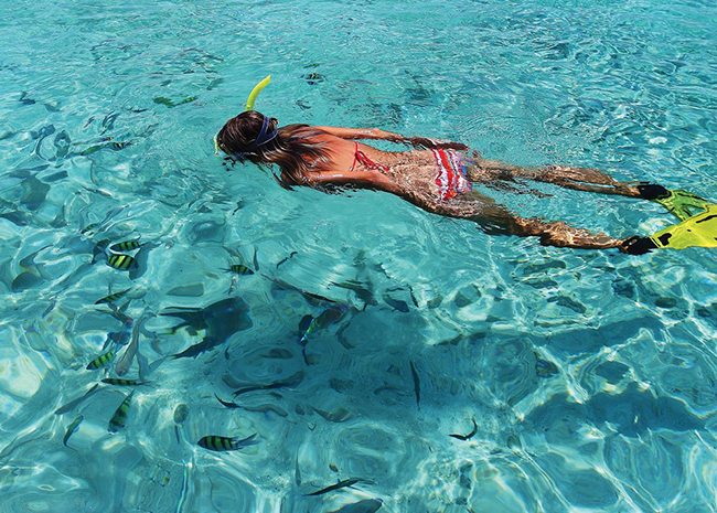 Christina snorkeling on the surface of the crystal clear waters.